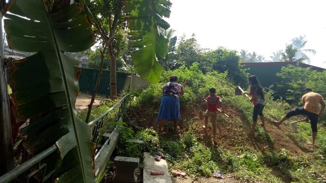 Het schoonmaken van de schooltuin met de ouders voor het nieuwe school trimester op zondag, 2 september, 2018.